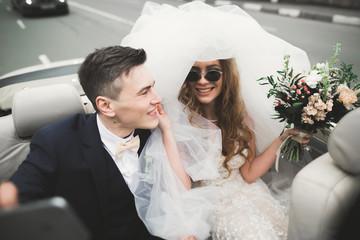 Happy bride and groom making selfie at their wedding in retro car