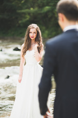 Elegant stylish happy brunette bride and gorgeous groom on the background of a beautiful river in the mountains