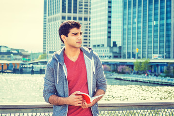 East Indian American college student studying in New York, wearing red v neck shirt, gray hooded sweatshirt, standing in business district, reading red book, thinking. Instagram filtered effect..