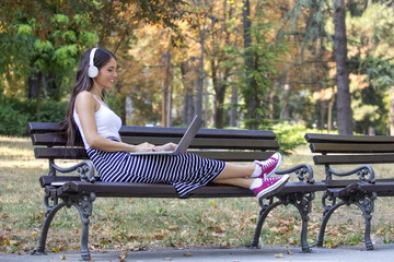Young beautiful girl sitting at the bench with headphones and notebook on her knees in park