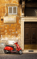 Narrow street in Rome with a typical red vespa scooter on a cobblestone street