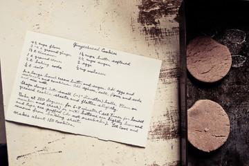 Gingerbread cookies on a baking sheet with handwritten recipe card.
