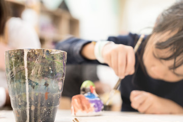 Girl in Art class blurred with Plastic colored glass foreground