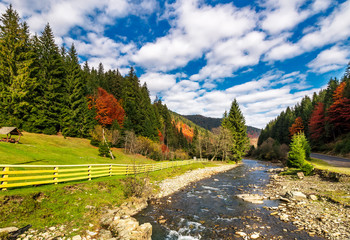 small river in spruce forested mountains with some trees in red foliage. camping place behind the fence on a grassy meadow. gorgeous landscape under vivid cloudy sky on fine autumn day