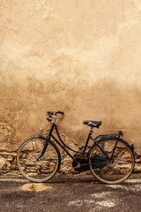 Verona.  Retro styled image of vintage old  Bicycle on Street in Italy, parking near wall with copy space.