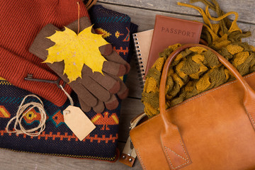 The concept of autumn holidays - bag, passport, maple leaves, key with blank label, warm clothes: a hat, pullover and gloves on a brown wooden background