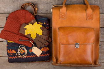 The concept of autumn holidays - bag, maple leaves, key with blank label, warm clothes: a hat, pullover and gloves on a brown wooden background