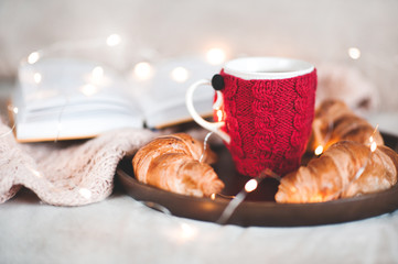 Cup of tea with cakes staying on wooden tray in room at Christmas lights on background. Good morning. Breakfast.