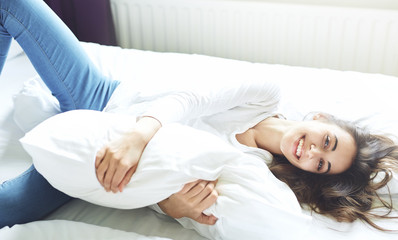young smiling woman lying on bed hugging pillow