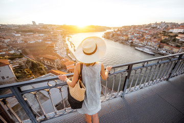 Young woman tourist enjoying beautiful landscape view on the old town with river standing on the iron bridge during the sunset in Porto city, Portugal