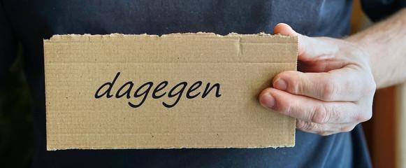 """Schild aus Pappe mit der Aufschrift """"dagegen"""""""
