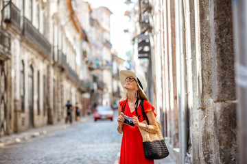Young woman tourist in red dress walking the street in the old town of Porto city, Portugal
