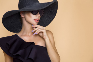 Portrait of an elegant woman in a hat and sunglasses on a beige background
