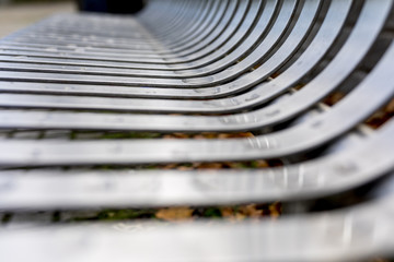 Close up of contemporary modern stainless steel street or park bench with rain drops on that makes an interesting abstract background or architectural feature