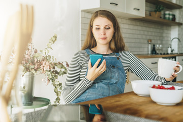 A young pregnant woman is sitting in the kitchen at the table, having breakfast, drinking tea and using a smartphone. Lifestyle, social network. Online marketing, education, blogging, chatting.