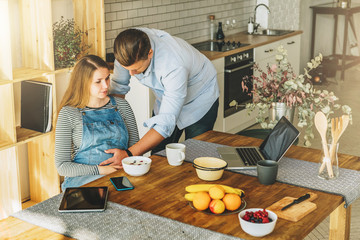 View from above.Morning, breakfast.Young married couple in kitchen.Pregnant woman is sitting at table, man is holding her pregnant belly.On table is laptop,tablet computer,dishes, fruits. Lifestyle.