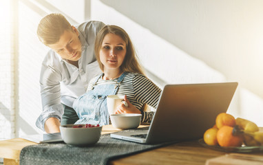 Front view.Morning, breakfast.Young married couple in kitchen.Pregnant woman is sitting at table and using laptop, man is holding her pregnant belly, looking on computer monitor. Lifestyle.
