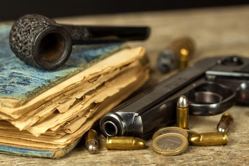 Gun and old book. Detective novel. Wooden tobacco pipe. Pistols and cartridges on the table.