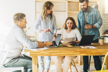 Teamwork, brainstorm. Group of young businesspeople work together in office at table, reading paper documents, uses laptops. Online marketing, education, e-learning.Startup, freelance, business