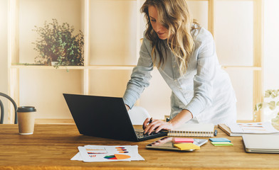 Young businesswoman woman is standing near kitchen table,uses laptop,working, studying.On table tablet computer,paper graphs.Student studying.Online marketing,education,e-learning. Lifestyle, startup
