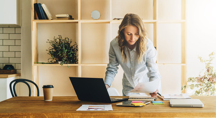 Young businesswoman woman is standing near kitchen table,reading documents,uses laptop,working, studying.On table tablet computer,paper graphs.Student studying.Online marketing, education, e-learning.