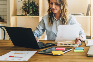 Young businesswoman woman is sitting at kitchen table and uses laptop, working, studying. On table tablet computer, paper documents. Freelancer works at home. Online marketing, education, e-learning.
