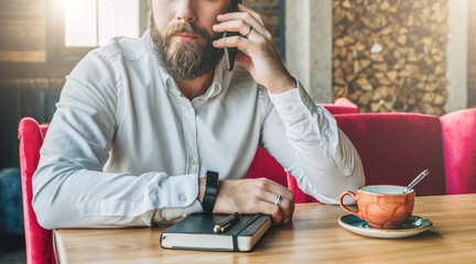 Young serious bearded businessman in white shirt is sitting in cafe at table and talking on his mobile phone. On table is notebook and cup of tea. Online education, marketing. Lifestyle, startup.
