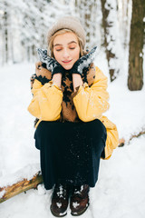 Odd bizarre female lying on tree in snowy winter forest. Beautiful young lovely girl relaxing outdoor. Unusual woman on vacation resting at nature. Lonely lady traveling in frost cold weather day.