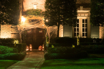 The house is decorated for Halloween: the entrance to the house is tightened with cobwebs, pumpkins with carved mugs and glowing from within. Night