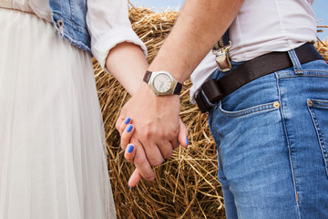 hands of a guy with chases and a girl in the background of a haystack