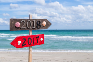Metal 2018 and 2017 number on the wooden beach sign standing at the beach.
