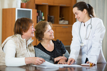 Female therapeutist consulting senior patients in clinic