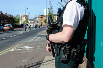 PSNI police officer stands on the Falls Road, Belfast, armed with a G36C automatic assault rifle.
