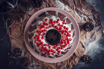 Marble cake with chocolate with pomegranates on the table,high angle