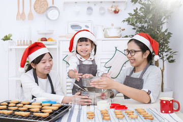 Little asian girl and her mother baking cake and cookies in the kitchen christmas eve holiday celebration. Happy asian family