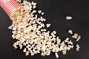 Popcorn horizontal banner. Red stripped paper cup and kernels lying on dark background. Copy space.