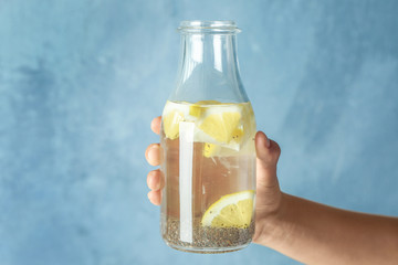 Hand holding bottle of water with chia seeds and lemon on light background