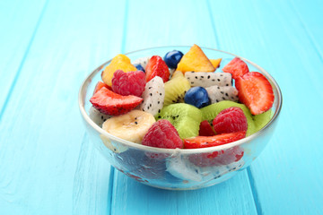 Bowl with delicious fruit salad on wooden table