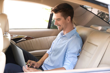 Young businessman using laptop in a car