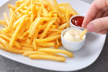 Woman eating yummy french fries with sauce, closeup