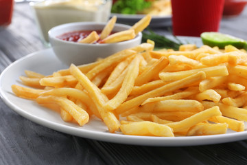 Plate with yummy french fries and sauce on table, closeup
