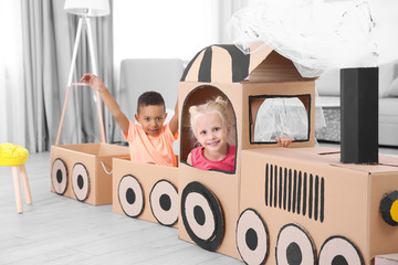 Cute children playing with cardboard train at home