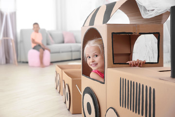 Cute girl in cardboard train at home