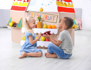 Cute kids sitting near counter with fruits indoors