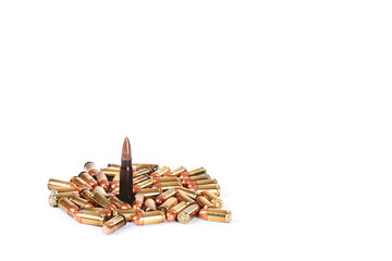 One large caliber bullet standing among a pile of smaller caliber bullets against a white background.