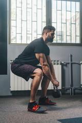 Muscular man workout with kettlebell