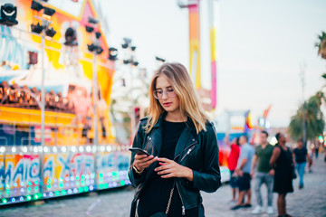 Trendy influencer modern millennial hipster teenager or cool fashionable woman stands in center of country fair or carnival or festival, uses smartphone app to stay connected on social media