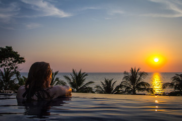 Woman enjoying the romantic sunset in a pool