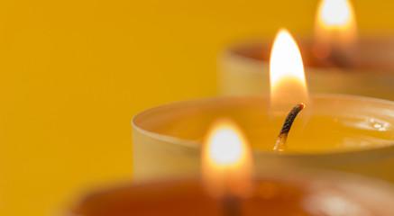 Drei brennende Teelichte mit weichem Hintergrund