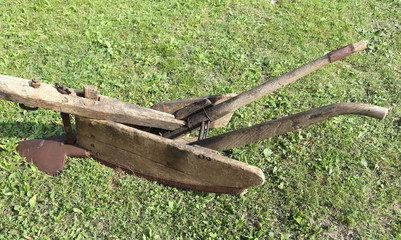 wooden ancient plow over meadow
